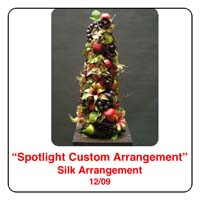 December Spotlight Christmas Flower Arrangement using grapes, apples, lillies in a cone shape topiary
