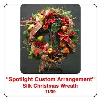 November Spotlight Christmas Wreath Arrangement using cinammon sticks, plaid ribbon, pears, apples, pomegrantes, artificial berries, christmas pine, pinecones, and cedar